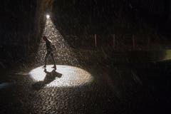 Ein Scheinwerfer und Schneefall bringen Licht ins Dunkel. (Bild: Urs Flüeler / Keystone (Luzern, 9. Januar 2019))