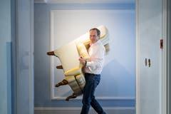 Der Hoteldirektor schleppt einen Sessel aus einer Suite.