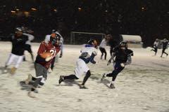 Neben Passspielzügen hat der Quarterback (rotes Trikot) auch die Möglichkeit, den Ball seinem Running Back zu übergeben, der versucht möglichst weit nach vorne zu laufen. Der Quarterback kann den Ball aber auch selbst nach vorne tragen.
