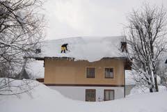 Zwei Männer schaufeln Schnee von einem Dach in Filzmoos, Österreich. (Bild: Christian Bruna / EPA)