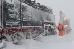 Mitarbeiter versuchen den Zug vom Schnee zu befreien. (Bild: Matthias Bieri (Schierke, 9.1.2019))
