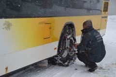 Der Chauffeur montiert in Wildhaus Dorf Schneeketten auf das Doppelstock-Postauto.(Bild: Adi Lippuner)