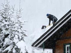 Ein Mann befreit ein Dach von der Schneelast am Mittwoch in der Nähe von Untertauern in Österreich. (Bild: Keystone/APA/APA/HELMUT FOHRINGER)