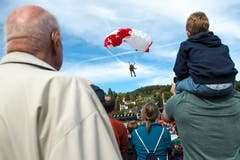 Zuschauer beobachten den Absprung der Fallschirmspringer mit anschliessender Landung in der Arena im Verkehrshaus. (Bild: Dominik Wunderli, Luzern, 12. Oktober 2019)