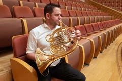 Ein Hornist stimmt sein Instrument.