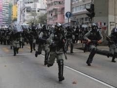 Trotz eines Polizeiverbots haben in Hongkong wieder Zehntausende Menschen gegen die Regierung protestiert. Während Demonstranten in einem langen Marsch friedlich durch den Stadtteil Kowloon zogen, gingen radikale Aktivisten auf einen Zerstörungszug durch die Stadt. (Bild: Keystone/AP/KIN CHEUNG)