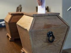 In Guttannen werden die Wahl- und Abstimmungszettel noch in eine Holzurne eingelegt. (Bild: KEYSTONE/PETER SCHNEIDER)