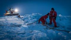 Forscher vergraben ein Stromkabel im Eis. (Bild: Stefan Hendricks / Alfred-Wegener-Institut, Antarktis, 16. Oktober 2019)