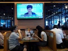 Das Fernsehen überträgt die Verkündung des Vermummungsverbot für Demonstranten durch die Hongkonger Regierungschefin Carrie Lam. (Bild: KEYSTONE/AP/VINCENT YU)