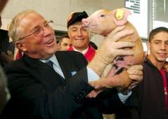 62. Olma: Bundesrat Christoph Blocher hält ein Säuli in die Kameras. (Bild: Keystone/Regina Kühne, 7. Oktober 2004)