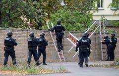 Polizisten klettern über die Wand, welche einen Friedhof umgibt. (EPA/FILIP SINGER)