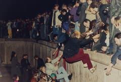 Ostberliner helfen Westberlinern in der Nacht über die Mauer. (Bild: Jockel Finck / Keystone, 9. November 1989)