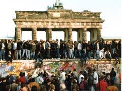 Am Tag nach der Öffnung am 9. Nov. 1989 steigen Menschen am 10. Nov. 1989 auf die Berliner Mauer vor dem Brandenburger Tor in Berlin. (Bild: KEYSTONE/AP/STR)