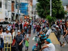 Venezolanerinnen und Venezolaner gehen in San Antonio zu Fuss über die Grenze nach Kolumbien. Einige kaufen im Nachbarland Essen und Medikamente, andere verlassen Venezuela für immer. (Bild: KEYSTONE/AP/FERNANDO LLANO)
