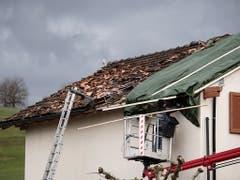 Ein Handwerker repariert ein abgedecktes Dach. (Bild: KEYSTONE/GIAN EHRENZELLER)