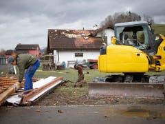 Ein Hausbesitzer zieht Nägel aus seinem abgedeckten Dach. (Bild: KEYSTONE/GIAN EHRENZELLER)