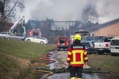 Die Feuerwehr verhindert mit ihrem Löscheinsatz das Übergreifen des Feuers auf umliegende Gebäude. (Bild: Dominik Wunderli)