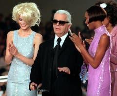 Kar Lagerfeld, umringt von den Models Claudia Schiffer (links) und Naomi Campbell, anlässlich einer Kollektionsvorstellung 1996 in Paris. (Bild: Remy de la Mauvinière / AP)