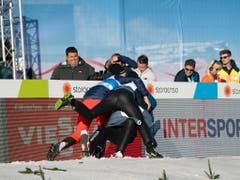 Die Teamkollegen jubeln mit: Killian Peier wird von Simon Ammann und Andreas Schuler umarmt und zu Boden gerissen (Bild: KEYSTONE/EPA/CHRISTIAN BRUNA)