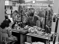 Besucher und eine Arbeiterin in der Maschinenhalle an der Mustermesse im Jahr 1960. (Bild: KEYSTONE/STR)
