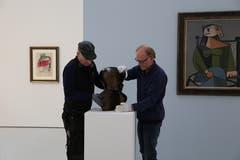 Jeder Griff sitzt: Würth-Mitarbeiter platzieren eine Bronze-Skulptur von Hans Arp. Ein Gemälde von Pablo Picasso (rechts) hat seinen Platz bereits gefunden, ebenso der Frauenkopf von Fernand Léger aus dem Jahr 1953 (links). (Bild: Jolanda Riedener)