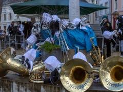 Die Guggenmusik Grachsymphoniker macht eine Pause am Cortege des ersten der «Drey scheenschte Daeaeg» in Basel. Bei diesem Aprilwetter waren Stärkungen gefragt. (Bild: KEYSTONE/GEORGIOS KEFALAS)