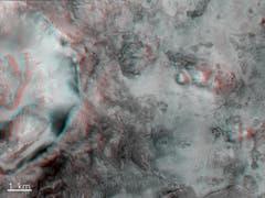 Ein Krater und unebenes Terrain zwischen den Syrtis und Isidis-Regionen des Mars. Das Bild kann mit einer rot-blauen Stereobrille betrachtet werden, um einen Eindruck der Tiefe zu erhalten. (Bild: ESA/Roskosmos/CaSSIS)