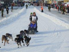 Martin Buser (Nummer 21) mit Team beim Show-Start für das diesjährige Iditarod am 2. März in Anchorage (Bild: KEYSTONE/FR7726 AP/MICHAEL DINNEEN)