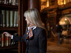 Eine Angestellte der Stiftsbibliothek trägt die neue Uniform. Das Konzept stammt von der jungen St. Galler Designerin Karin Bischoff, für das Design war das Unternehmen Jakob Schlaepfer zuständig. (Bild: Keystone/Gian Ehrenzeller)