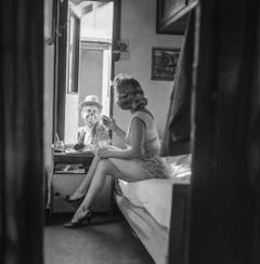 Eine Zirkusartistin des Circus Knie sitzt in ihrem Wohnwagen auf dem Bett und unterhält sich mit einem Clown, aufgenommen in Rapperswil am 17. März 1961. (Bild: Keystone /Str)