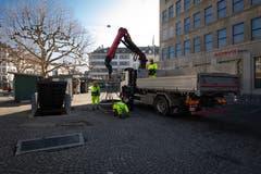 Mitarbeiter von Stadtgrün St.Gallen platzieren auf dem Markptlatz neue Pflanzkübel. Unter anderem auch in der Lücke zwischen den grünen Markthäuschen des ständigen Marktes.