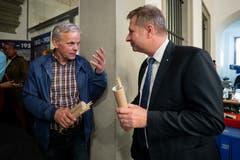 Rudolf Schweizer (parteilose Schweizer, links) verteilt Marcel Schwerzmann (parteilos) ein Geschenk. (Bild: Philipp Schmidli)