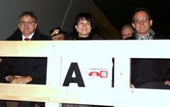 An der Eröffnung des A8-Tunnels in Lungern (von links): Landammann Franz Enderli , Bundesrätin Doris Leuthard und Baudirektor Paul Federer fahren auf dem Tiefladewagen zum Lichtspektakel in den neuen Tunnel. (Bild: Romano Cuonz, 10. Dezember 2012)