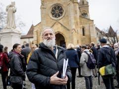 Auf dem Platz der Kollegiatskirche in Neuenburg versammelten sich die Unterstützer des Pastors Norbert Valley (vorne). (Bild: Keystone/JEAN-CHRISTOPHE BOTT)
