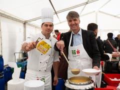 Berns Stadtpräsident Alec von Graffenried und Foodwaste-Pionier Mirko Buri schöpfen Suppe am Jubiläumsfest von Brot für alle, Fastenopfer und Partner sein. (Bild: Brot für alle/Patrik Kummer)