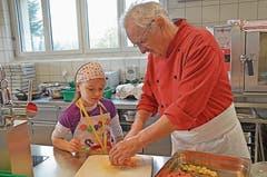 Der Küchenchef Erich Bollhalder zeigt den Schülerinnen und Schülern geduldig, was nacheinander zu erledigen ist.