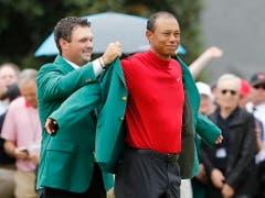 Vorjahressieger Patrick Reed kleidet Tiger Woods in das berühmte Grüne Jackett ein (Bild: KEYSTONE/EPA/ERIK S. LESSER)