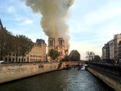Die weltberühmte Kathedrale Notre-Dame in Paris brennt. Graue Rauchwolken stiegen in die Höhe und waren kilometerweit zu sehen. (Bild: KEYSTONE/AP/LORI HINANT)