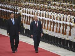 Bundespräsident Ueli Maurer und der chinesische Präsident Xi Jinping schreiten die Ehrengarde ab. (Bild: Keystone/AP/MADOKA IKEGAMI)