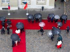 Mit Schirmen auf dem Roten Teppich: Das Erbprinzenpaar, die Schweizer Landesregierung, Weibel und andere Offizielle beim Staatsempfang. (Bild: KEYSTONE/PETER KLAUNZER)