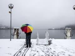 Ein Mann steht mit dem Regenschirm bei der Schiffstation in Brunnen SZ am Donnerstag. (Bild: Keystone/ALEXANDRA WEY)
