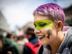 Farbe und ein Lächeln müssen auch sein: Junge Frau an der Klimademo in Lausanne. (Bild: KEYSTONE/EPA KEYSTONE/VALENTIN FLAURAUD)