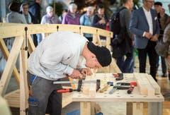 Ein Lehrling arbeitet konzentriert zwischen den Messebesuchern. (Bild: Reto Martin)