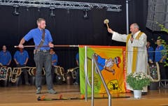 Pfarrer Josef Manser tauft und segnet die Fahne der Landjugend Alttoggenburg, die ihm der Fähnrich reicht. (Bild: Peter Jenni)