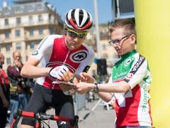 Roland Thalmann, der Fahrer vom Swiss Cycling Team, erfüllt einem Fan einen Autogrammwunsch. Das Dress des Schweizer Nationalteams ist von den Zuschauern am Strassenrand stets gut zu erkennen (Bild: KEYSTONE/JEAN-CHRISTOPHE BOTT)