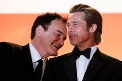 Der US-Regisseur Quentin Tarantino flüstert Brad Pitt etwas ins Ohr. > Filmpremiere «Once Upon A Time ... In Hollywood» (Bild: EPA/IAN LANGSDON)