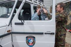 Daniel Seckler von der Schweizer Armee hilft Carlo Felder beim Anziehen der VR Brille, mit welcher er auf eine virtuelle Patrouillenfahrt gehen kann. (Bild: Boris Bürgisser, 1. Mai 2019)