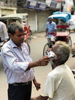 Ein Barbier am Strassenrand von New Delhi.