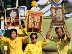 Lang lebe der König: Monarchisten in gelben Hemden halten Porträts ihrer neuen Königs in die Luft. (Bild: KEYSTONE/AP/SAKCHAI LALIT)