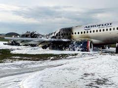 Löschschaum bedeckt die Rollbahn und das zerstörte Flugzeug. (Bild: KEYSTONE/AP Moscow News Agency)